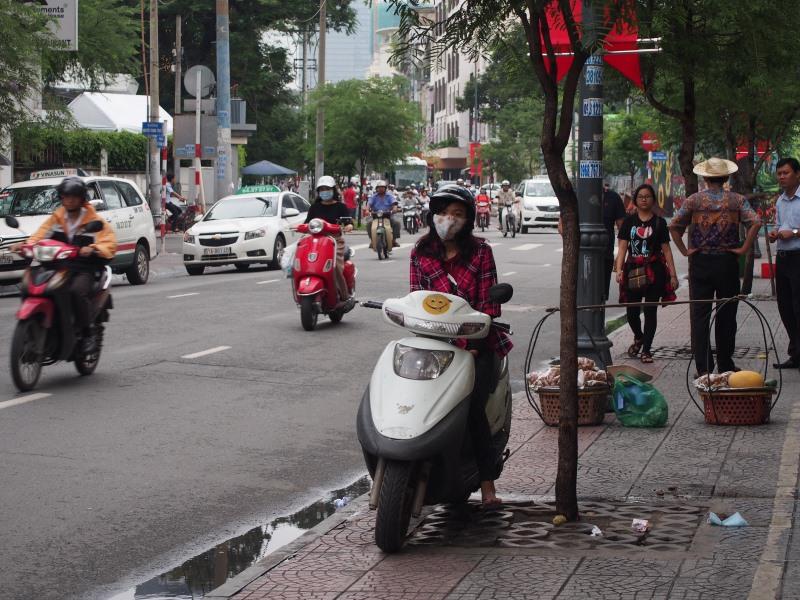 Une jeune fille en scooter dans les rues de Ho Chi Minh